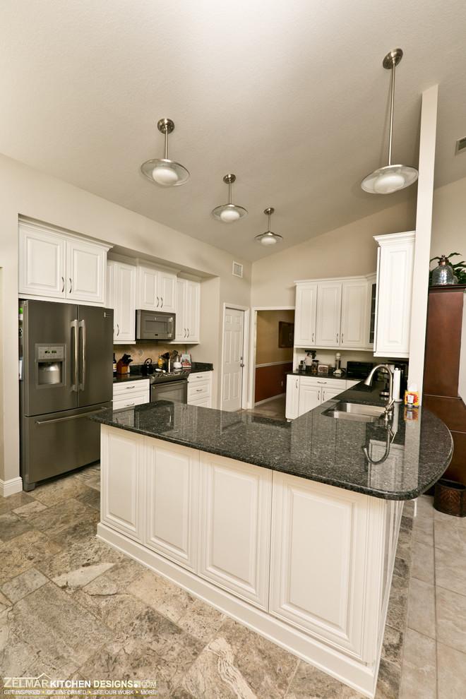 Eat-in kitchen - mid-sized transitional u-shaped travertine floor eat-in kitchen idea in Orlando with raised-panel cabinets, granite countertops, beige backsplash, stone tile backsplash and a peninsula