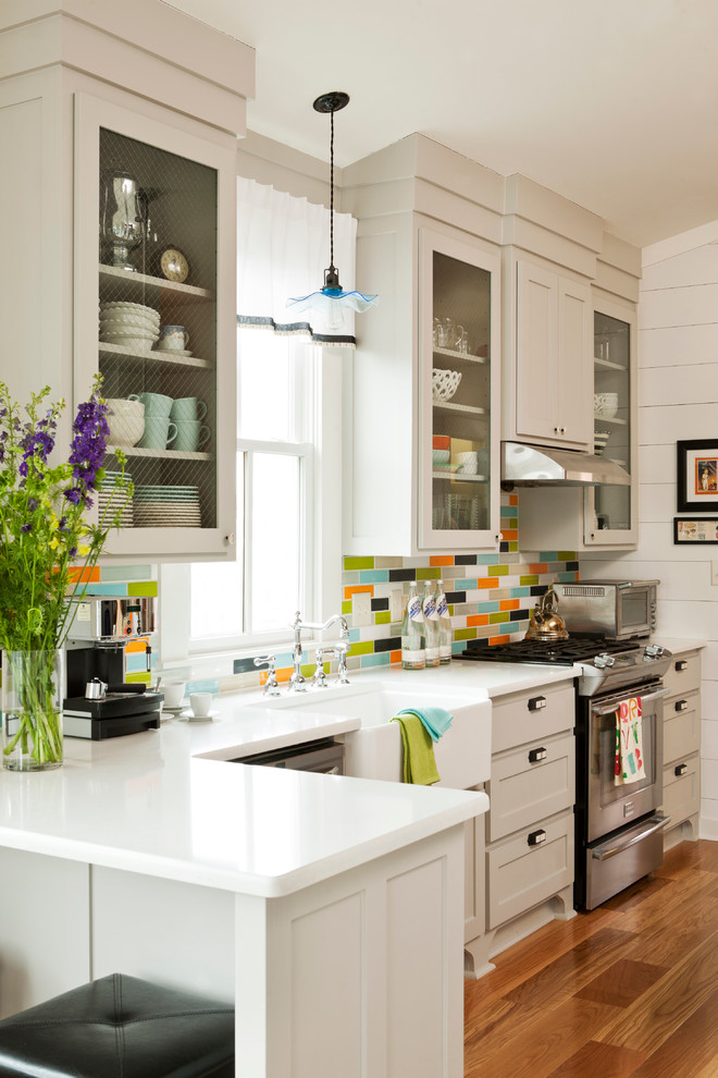 Inspiration for a timeless kitchen remodel in Little Rock with quartz countertops, multicolored backsplash, gray cabinets, glass-front cabinets and stainless steel appliances