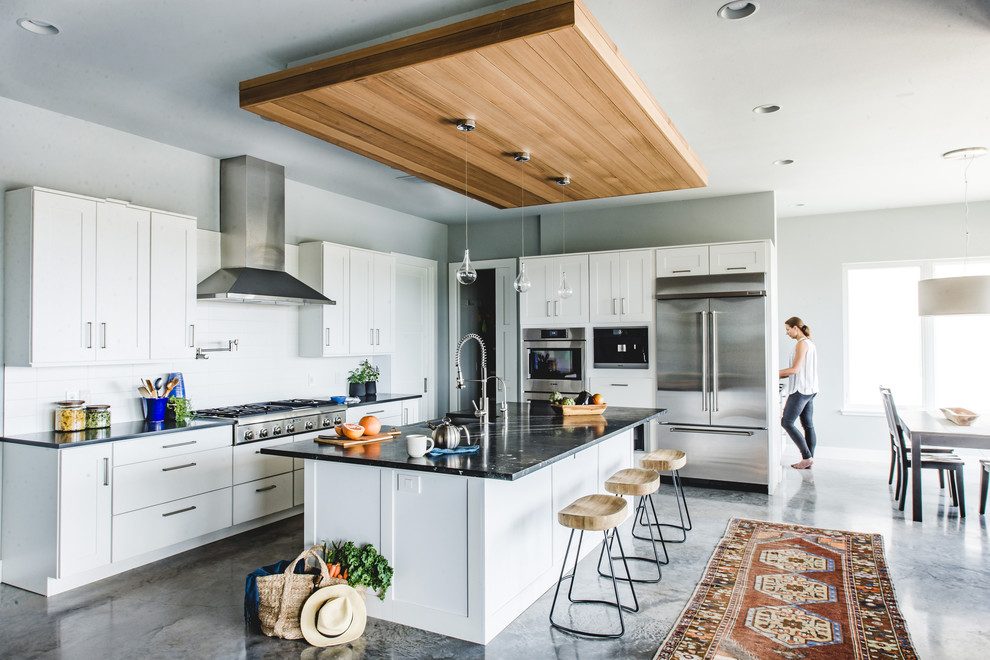 Eat-in kitchen - transitional l-shaped gray floor eat-in kitchen idea in San Francisco with shaker cabinets, white cabinets, white backsplash, subway tile backsplash, stainless steel appliances and an island