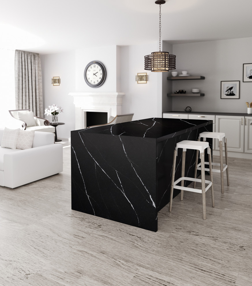 Example of a trendy kitchen design in Hampshire with quartzite countertops, black appliances and an island