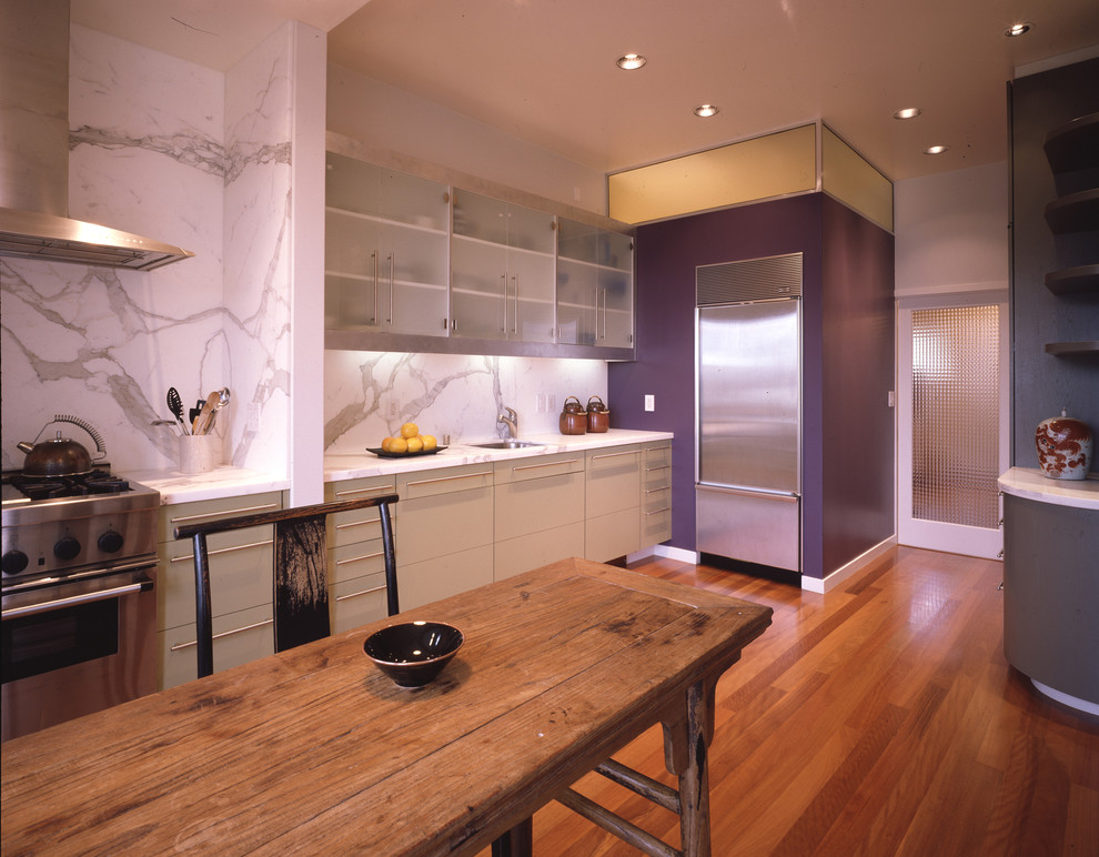 Trendy kitchen photo in San Francisco with stainless steel appliances, an undermount sink, glass-front cabinets, white cabinets, marble countertops, white backsplash and stone slab backsplash