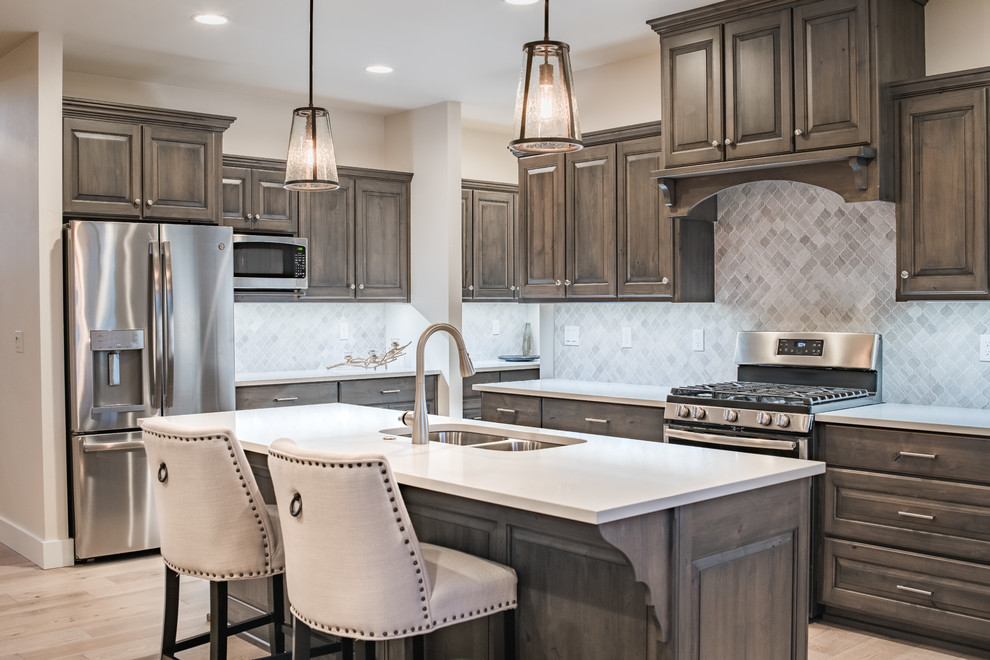 Example of a large transitional l-shaped light wood floor and beige floor kitchen design in Other with a double-bowl sink, raised-panel cabinets, quartz countertops, gray backsplash, ceramic backsplash, stainless steel appliances, an island, white countertops and dark wood cabinets