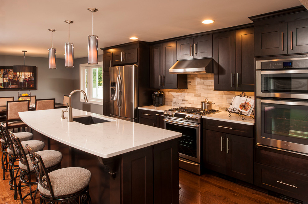 Example of a mid-sized trendy single-wall medium tone wood floor open concept kitchen design in New York with a single-bowl sink, recessed-panel cabinets, dark wood cabinets, quartz countertops, beige backsplash, stone tile backsplash, stainless steel appliances and an island