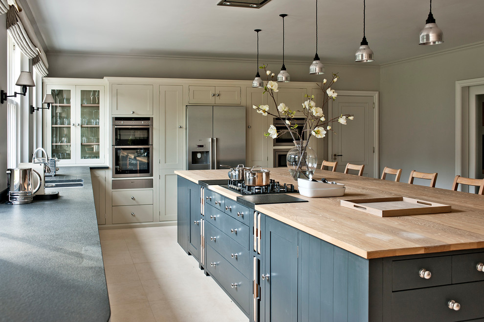 Large trendy enclosed kitchen photo in Gloucestershire with shaker cabinets, gray cabinets, wood countertops, stainless steel appliances and an island