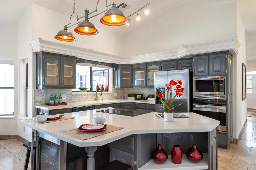 Elegant l-shaped beige floor kitchen photo in Phoenix with gray cabinets, gray backsplash, subway tile backsplash, stainless steel appliances, an island, white countertops and glass-front cabinets