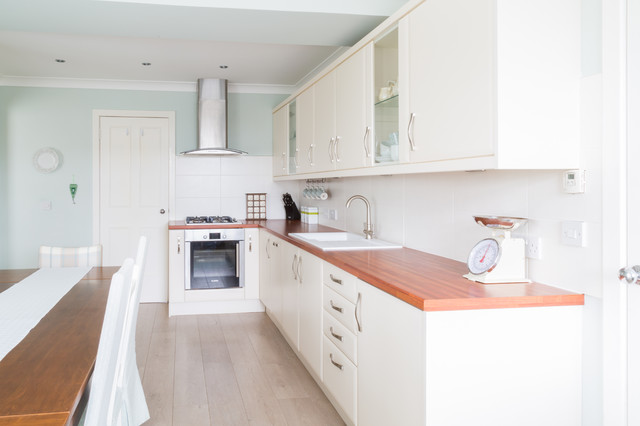 This is an example of a medium sized modern l-shaped kitchen/diner in Other with a built-in sink, flat-panel cabinets, beige cabinets, laminate countertops, beige splashback, ceramic splashback, stainless steel appliances and no island.