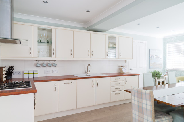 Photo of a medium sized modern l-shaped kitchen/diner in Other with a built-in sink, glass-front cabinets, beige cabinets, laminate countertops, beige splashback, ceramic splashback, stainless steel appliances and no island.