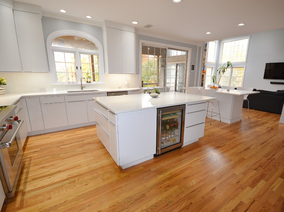 Eat-in kitchen - large scandinavian l-shaped medium tone wood floor and brown floor eat-in kitchen idea in Philadelphia with an undermount sink, flat-panel cabinets, white cabinets, quartz countertops, white backsplash, ceramic backsplash, stainless steel appliances and an island