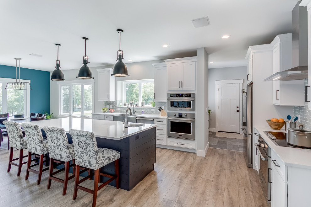 Example of a large transitional l-shaped beige floor eat-in kitchen design in Other with a farmhouse sink, shaker cabinets, white cabinets, gray backsplash, ceramic backsplash, stainless steel appliances, white countertops and an island