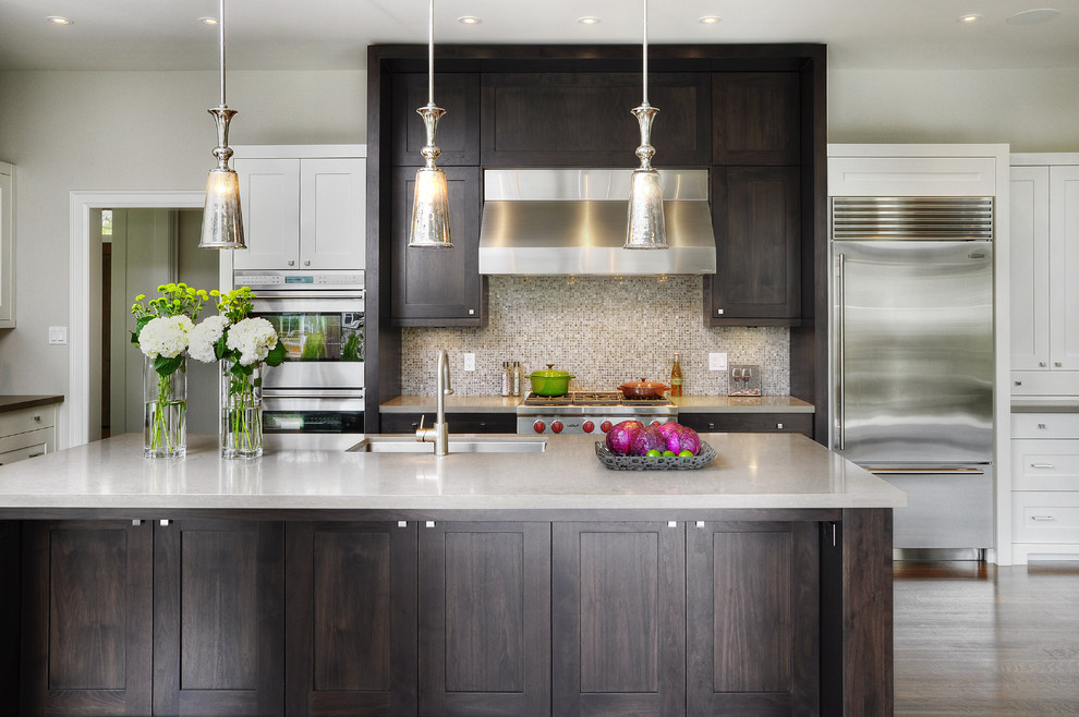 Inspiration for a transitional galley kitchen remodel in Toronto with mosaic tile backsplash, stainless steel appliances, an undermount sink, shaker cabinets, dark wood cabinets, brown backsplash and solid surface countertops