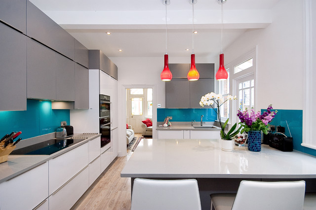 Trendy light wood floor kitchen photo in London with an undermount sink, flat-panel cabinets, white cabinets, blue backsplash, glass sheet backsplash and a peninsula