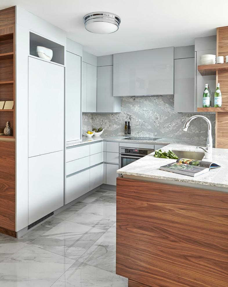 Modelo de cocinas en L actual, pequeña, con fregadero bajoencimera, armarios con paneles lisos, puertas de armario grises, salpicadero verde, salpicadero de losas de piedra, una isla y suelo blanco