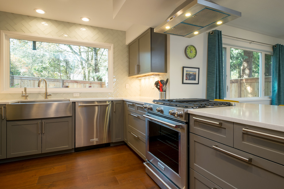 Mid-sized trendy u-shaped dark wood floor kitchen photo in Portland with an undermount sink, recessed-panel cabinets, gray cabinets, quartz countertops, white backsplash, glass tile backsplash, stainless steel appliances and a peninsula