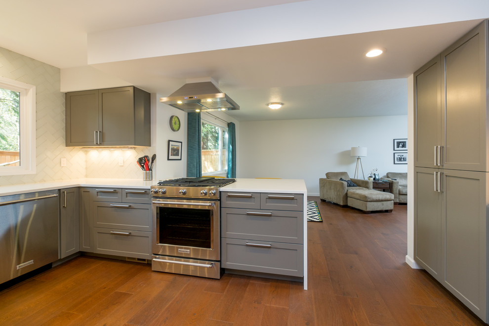 Kitchen - mid-sized contemporary u-shaped dark wood floor kitchen idea in Portland with an undermount sink, recessed-panel cabinets, gray cabinets, quartz countertops, white backsplash, glass tile backsplash, stainless steel appliances and a peninsula