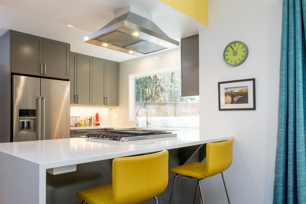 Example of a mid-sized trendy u-shaped dark wood floor kitchen design in Portland with an undermount sink, recessed-panel cabinets, gray cabinets, quartz countertops, white backsplash, glass tile backsplash, stainless steel appliances and a peninsula