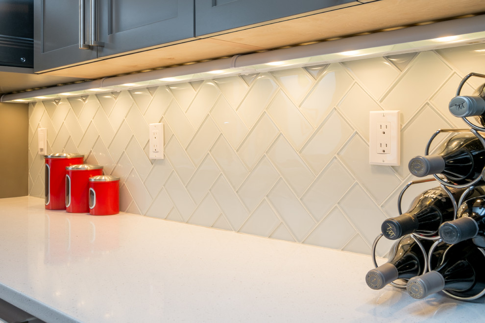 Inspiration for a mid-sized transitional u-shaped dark wood floor kitchen remodel in Portland with an undermount sink, recessed-panel cabinets, gray cabinets, quartz countertops, white backsplash, glass tile backsplash, stainless steel appliances and a peninsula