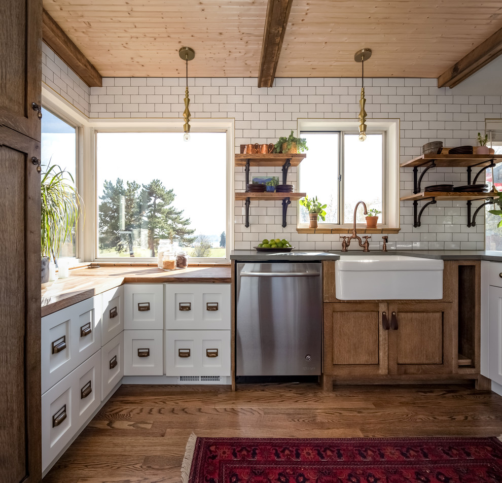 Small cottage u-shaped medium tone wood floor and brown floor kitchen photo in Denver with a farmhouse sink, shaker cabinets, wood countertops, white backsplash, ceramic backsplash, stainless steel appliances, a peninsula, white cabinets and brown countertops