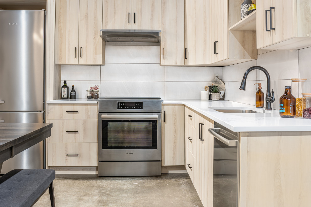 Inspiration for a small transitional l-shaped concrete floor and gray floor eat-in kitchen remodel in Calgary with an undermount sink, flat-panel cabinets, light wood cabinets, quartz countertops, gray backsplash, porcelain backsplash, stainless steel appliances, no island and multicolored countertops
