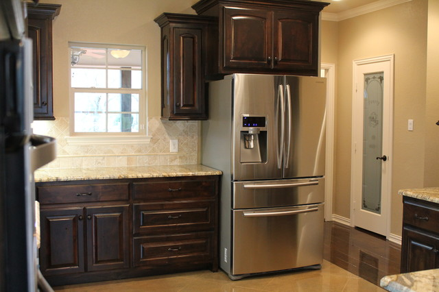 Inspiration for a timeless l-shaped eat-in kitchen remodel in Dallas with dark wood cabinets, granite countertops, beige backsplash, stone tile backsplash and stainless steel appliances