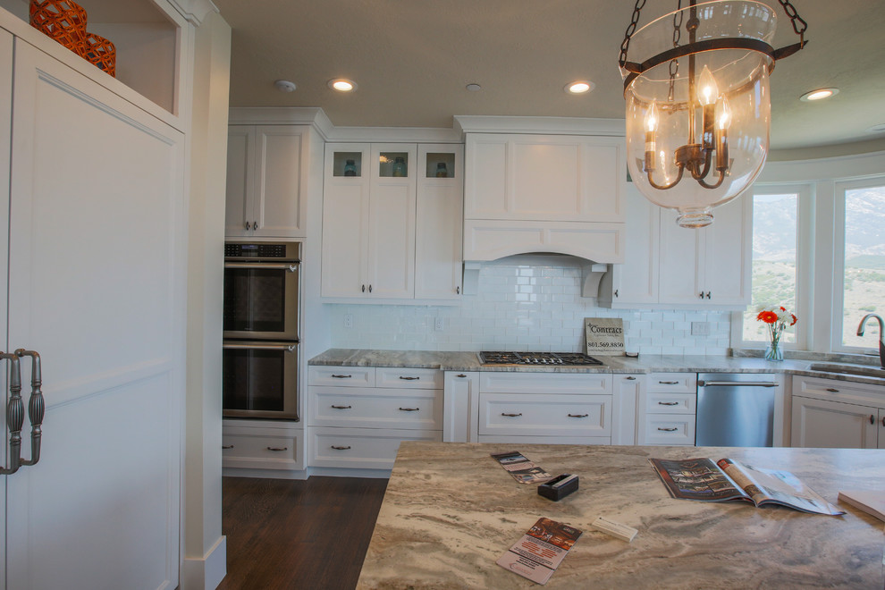 Open concept kitchen - large transitional medium tone wood floor open concept kitchen idea in Salt Lake City with an undermount sink, shaker cabinets, white cabinets, white backsplash, subway tile backsplash, paneled appliances and an island