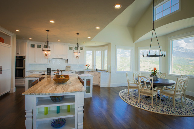 Large medium tone wood floor open concept kitchen photo in Salt Lake City with an undermount sink, shaker cabinets, white cabinets, white backsplash, subway tile backsplash, paneled appliances and an island