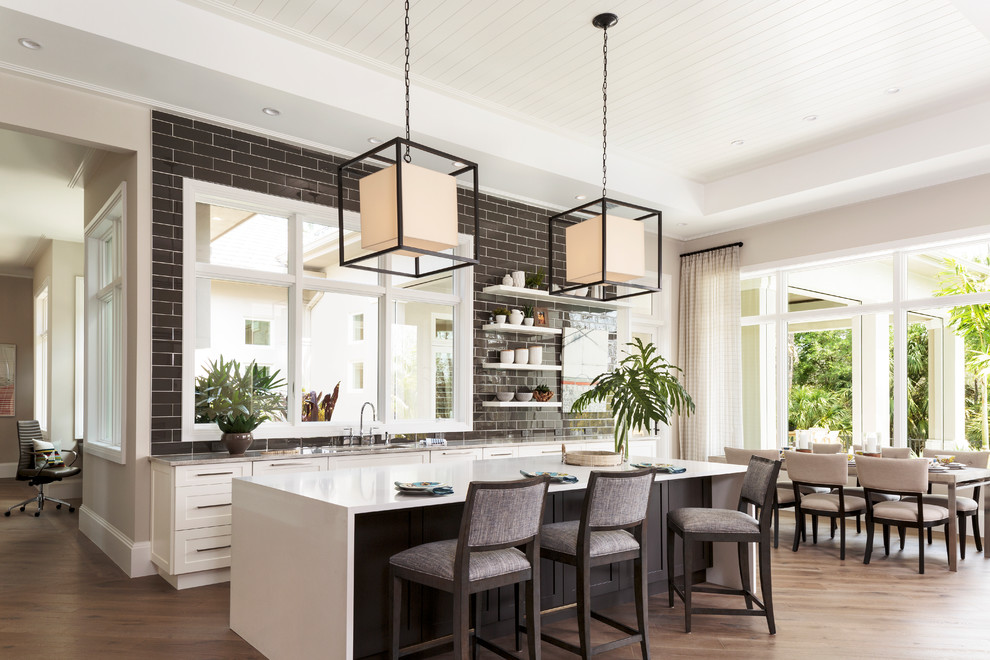 Mid-sized transitional single-wall dark wood floor and brown floor eat-in kitchen photo in Miami with an undermount sink, shaker cabinets, white cabinets, quartzite countertops, brown backsplash, subway tile backsplash and an island