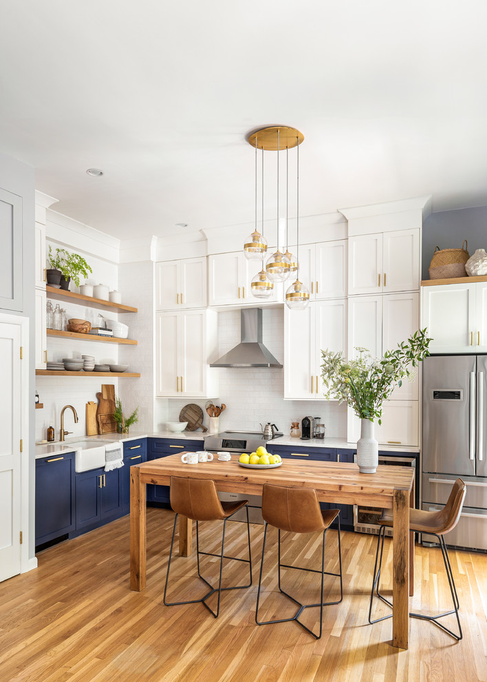 Inspiration for a transitional l-shaped medium tone wood floor and brown floor eat-in kitchen remodel in Boston with blue cabinets, white backsplash, ceramic backsplash, a farmhouse sink, shaker cabinets, no island and white countertops