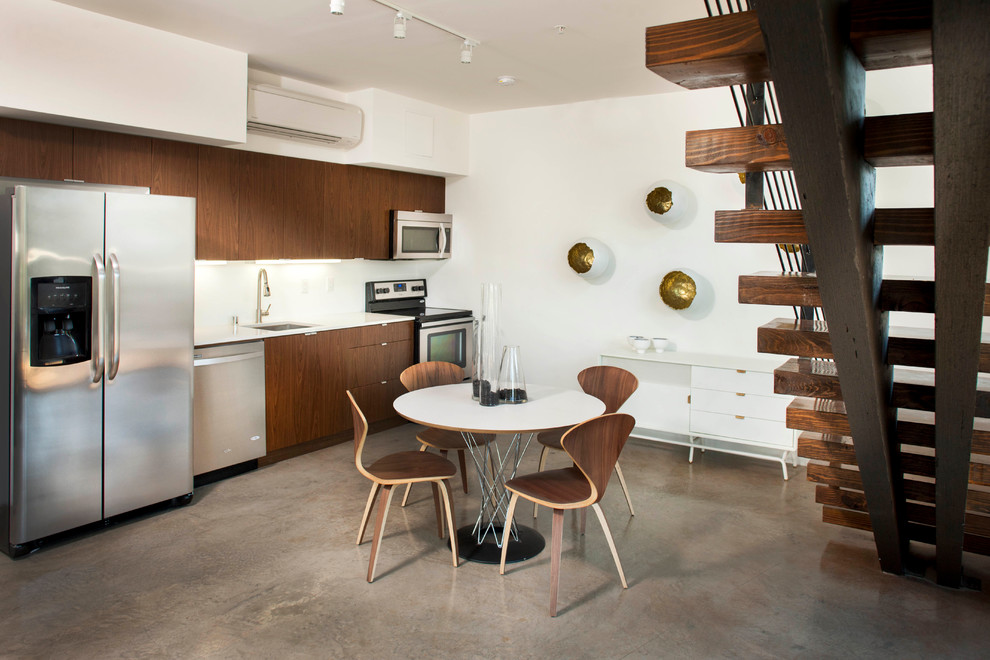 Eat-in kitchen - contemporary single-wall concrete floor eat-in kitchen idea in San Diego with an undermount sink, flat-panel cabinets, dark wood cabinets, stainless steel appliances and no island