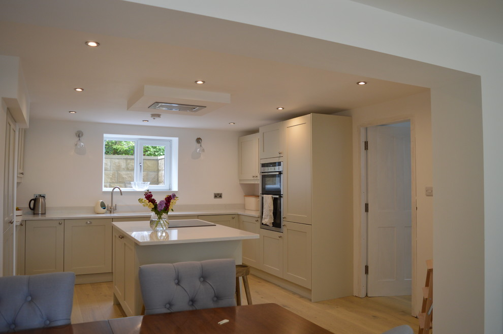 This is an example of a large contemporary kitchen/diner in Other with white cabinets, quartz worktops, black appliances, medium hardwood flooring and an island.