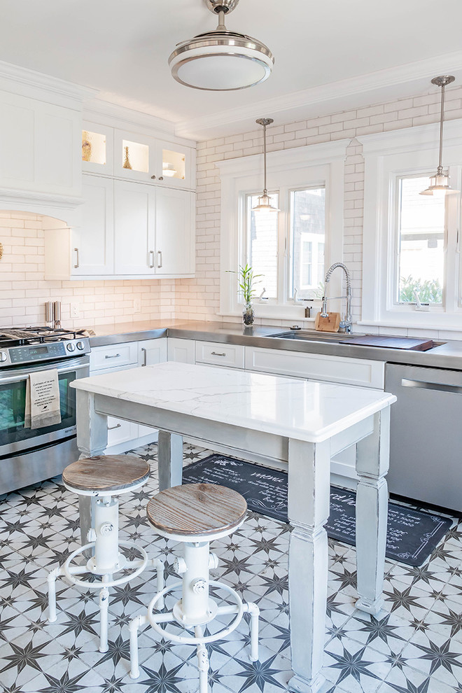 Example of a country l-shaped multicolored floor kitchen design in Philadelphia with an integrated sink, shaker cabinets, white cabinets, stainless steel countertops, white backsplash, subway tile backsplash, stainless steel appliances and an island