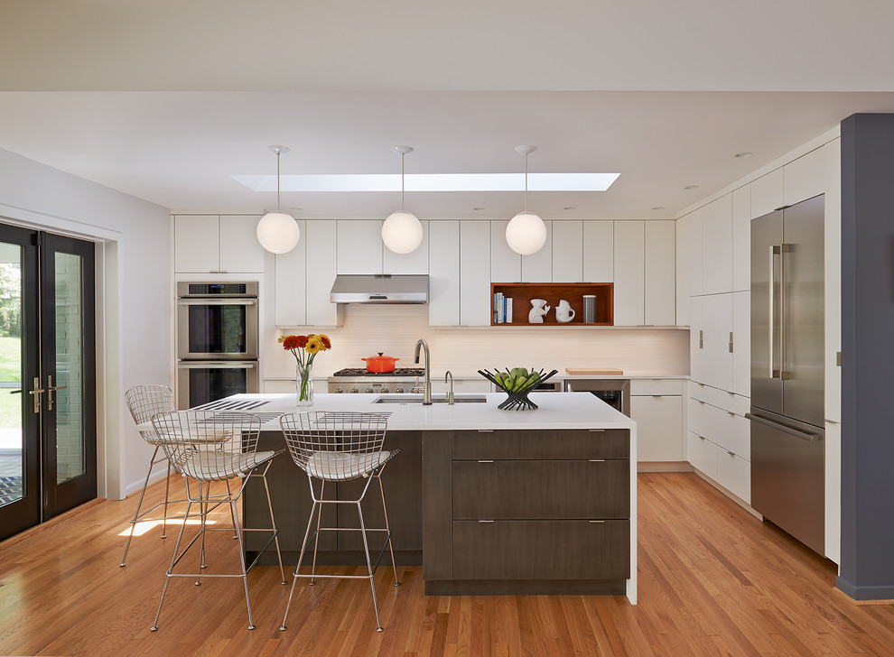 Example of a mid-sized 1960s l-shaped light wood floor and beige floor open concept kitchen design in DC Metro with flat-panel cabinets, white cabinets, an island, quartz countertops, white backsplash, ceramic backsplash, stainless steel appliances and an undermount sink