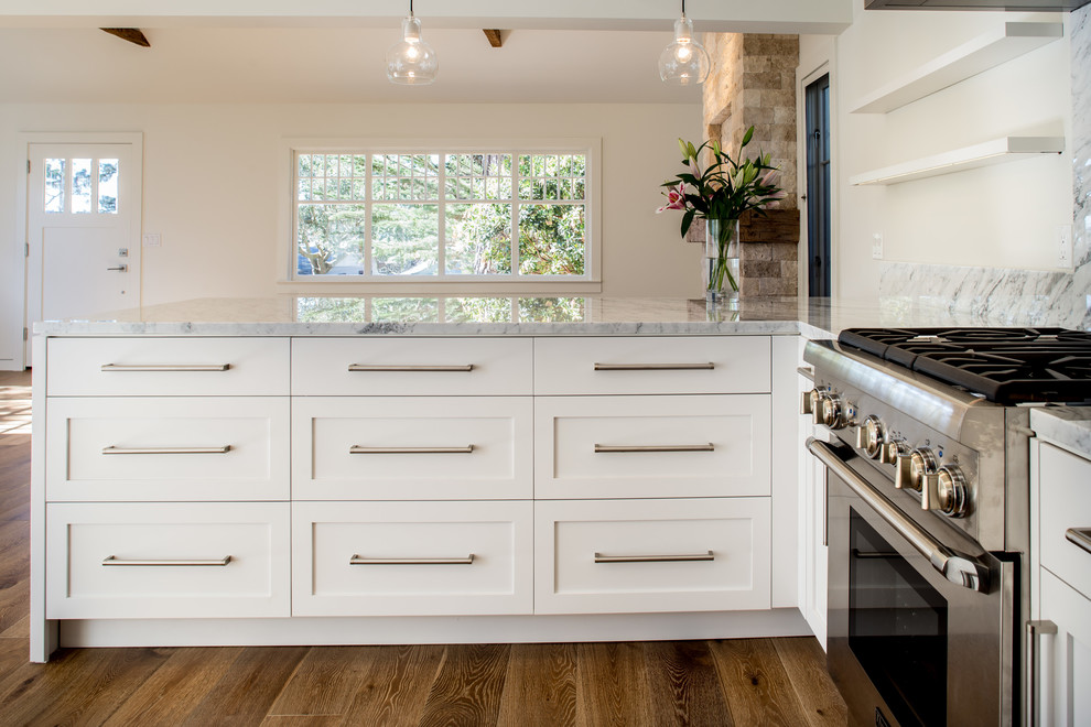 Example of a minimalist u-shaped medium tone wood floor open concept kitchen design in San Francisco with a farmhouse sink, shaker cabinets, white cabinets, marble countertops, white backsplash, stone slab backsplash, stainless steel appliances and a peninsula