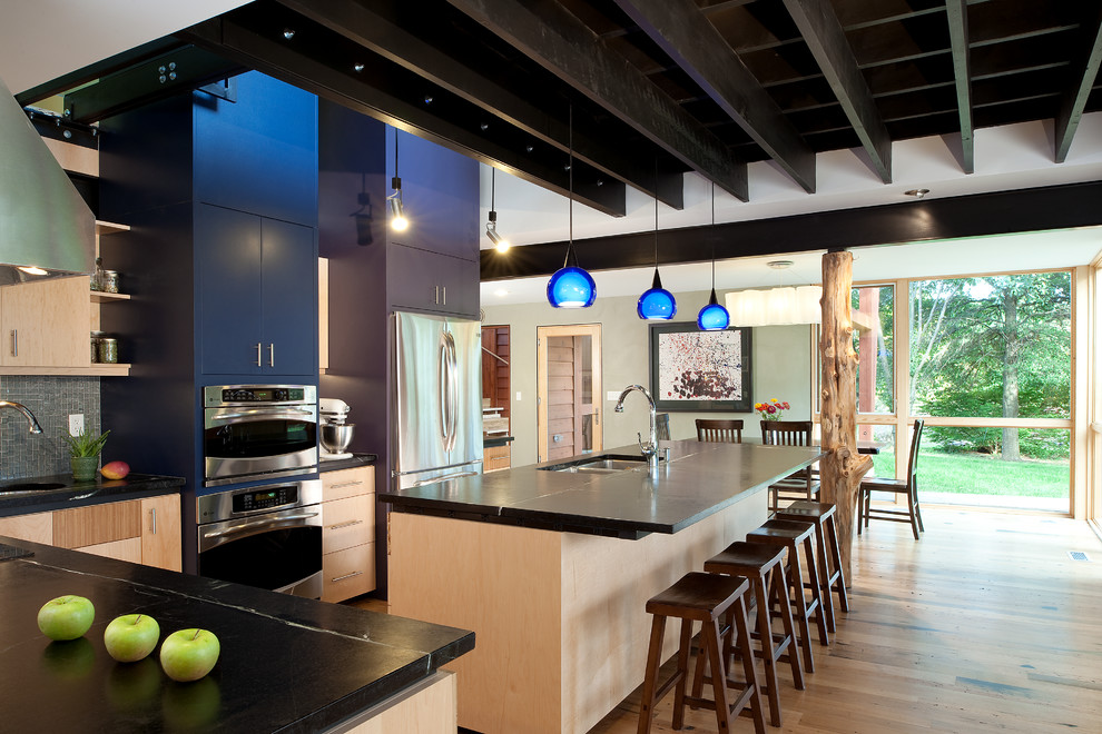 Eat-in kitchen - large contemporary l-shaped light wood floor eat-in kitchen idea in DC Metro with a double-bowl sink, flat-panel cabinets, light wood cabinets, granite countertops, stainless steel appliances, an island, glass tile backsplash and black countertops