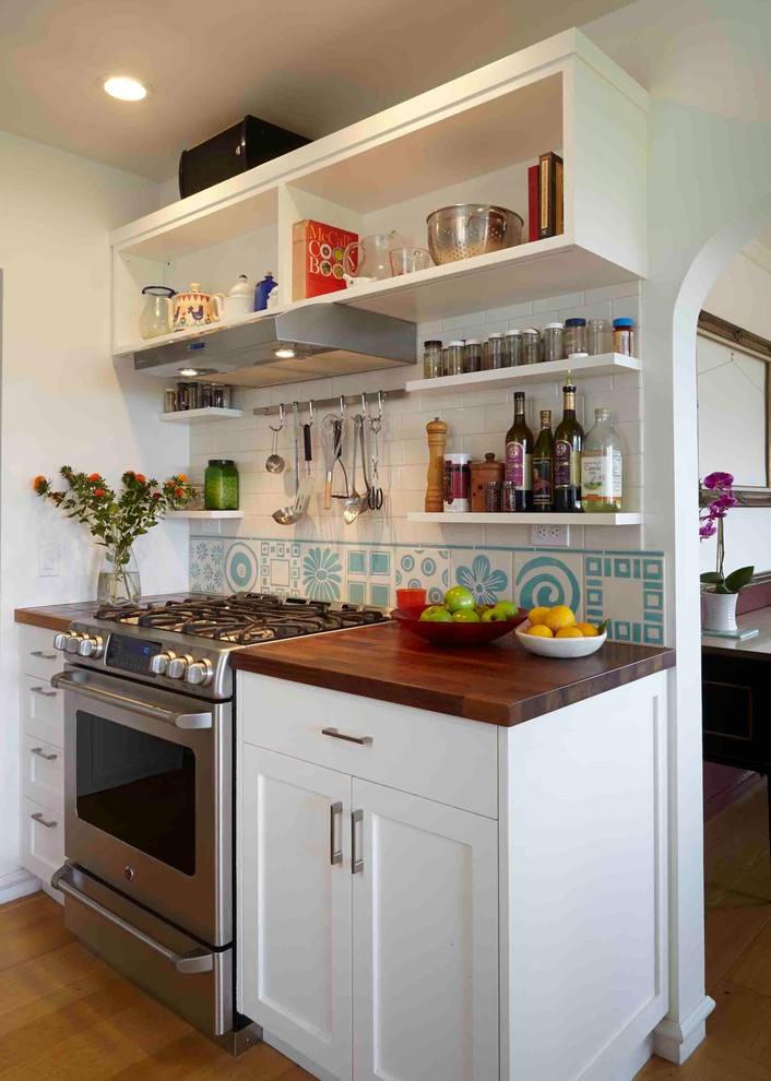 Inspiration for a transitional kitchen remodel in San Francisco with open cabinets, white cabinets, wood countertops, white backsplash and stainless steel appliances