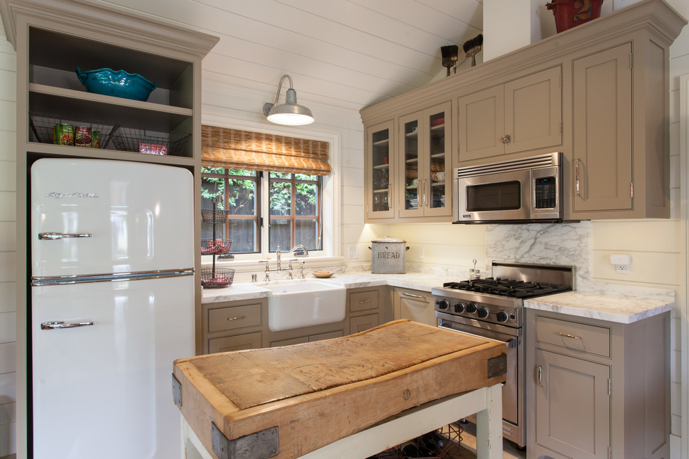 Inspiration for a small country l-shaped kitchen remodel in San Francisco with a farmhouse sink, beaded inset cabinets, stainless steel appliances, an island and beige cabinets