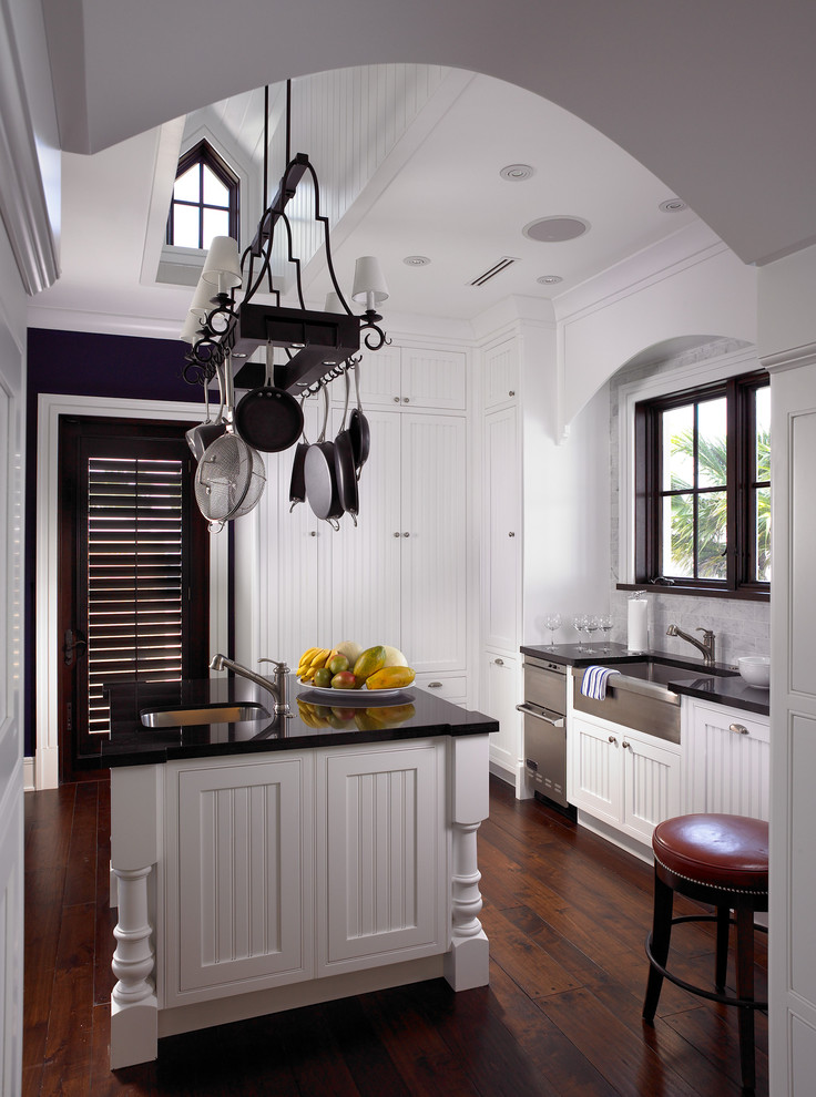 Elegant dark wood floor enclosed kitchen photo in Miami with a farmhouse sink, white cabinets, granite countertops, stone slab backsplash and an island