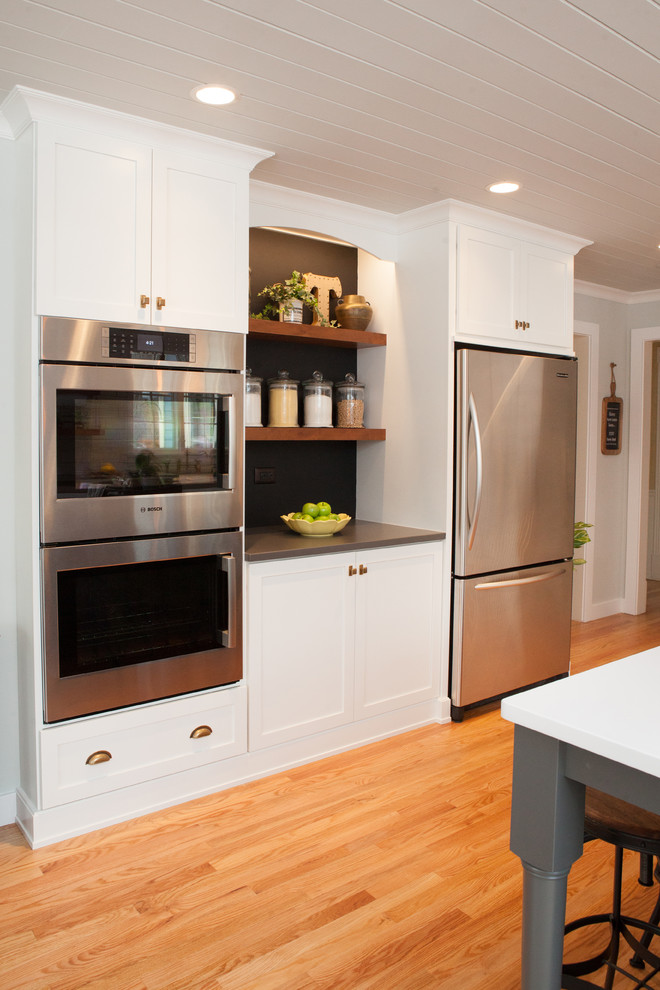 Eat-in kitchen - mid-sized transitional u-shaped light wood floor eat-in kitchen idea in Chicago with a farmhouse sink, recessed-panel cabinets, white cabinets, quartz countertops, multicolored backsplash, subway tile backsplash, stainless steel appliances and an island