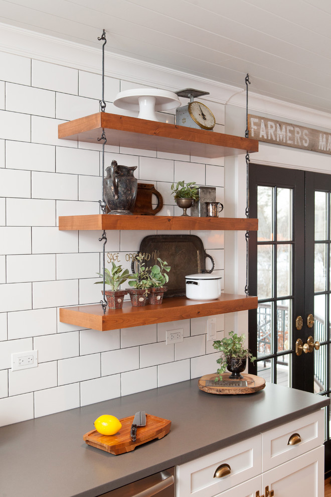 Inspiration for a mid-sized transitional u-shaped light wood floor eat-in kitchen remodel in Chicago with a farmhouse sink, recessed-panel cabinets, white cabinets, quartz countertops, multicolored backsplash, subway tile backsplash, stainless steel appliances and an island