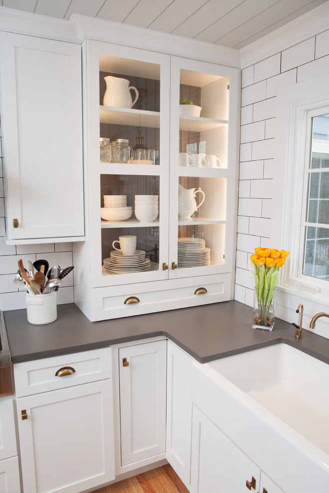 Mid-sized transitional u-shaped light wood floor eat-in kitchen photo in Chicago with a farmhouse sink, recessed-panel cabinets, white cabinets, quartz countertops, multicolored backsplash, subway tile backsplash, stainless steel appliances and an island