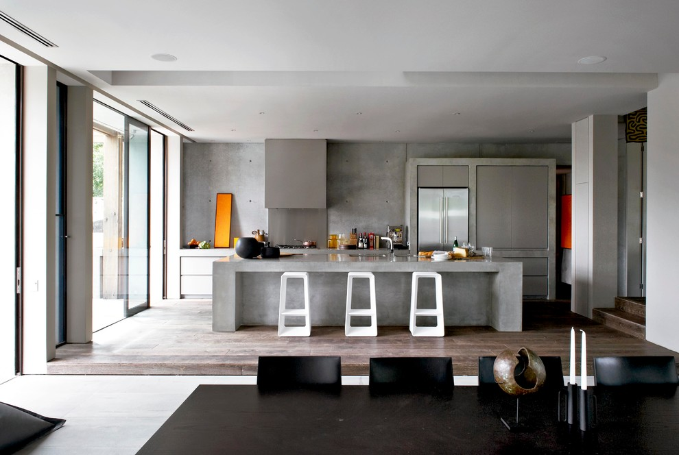 Trendy dark wood floor eat-in kitchen photo in Melbourne with flat-panel cabinets, gray cabinets, concrete countertops, cement tile backsplash, stainless steel appliances and an island