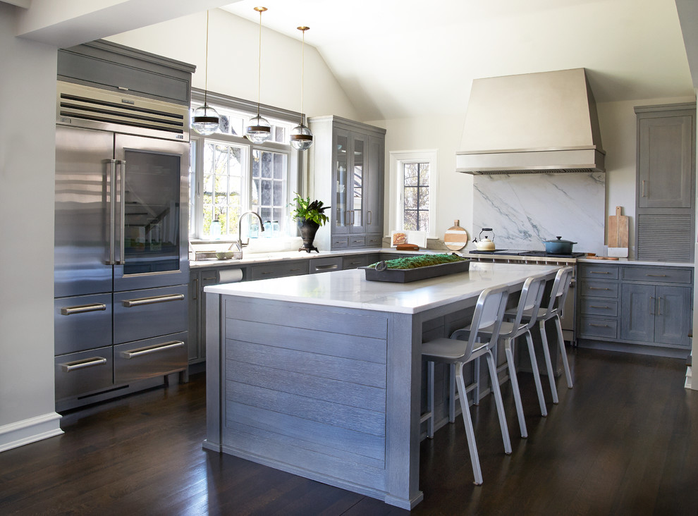 Inspiration for a large transitional l-shaped dark wood floor eat-in kitchen remodel in New York with an undermount sink, gray cabinets, quartzite countertops, gray backsplash, stone slab backsplash, stainless steel appliances, an island and shaker cabinets
