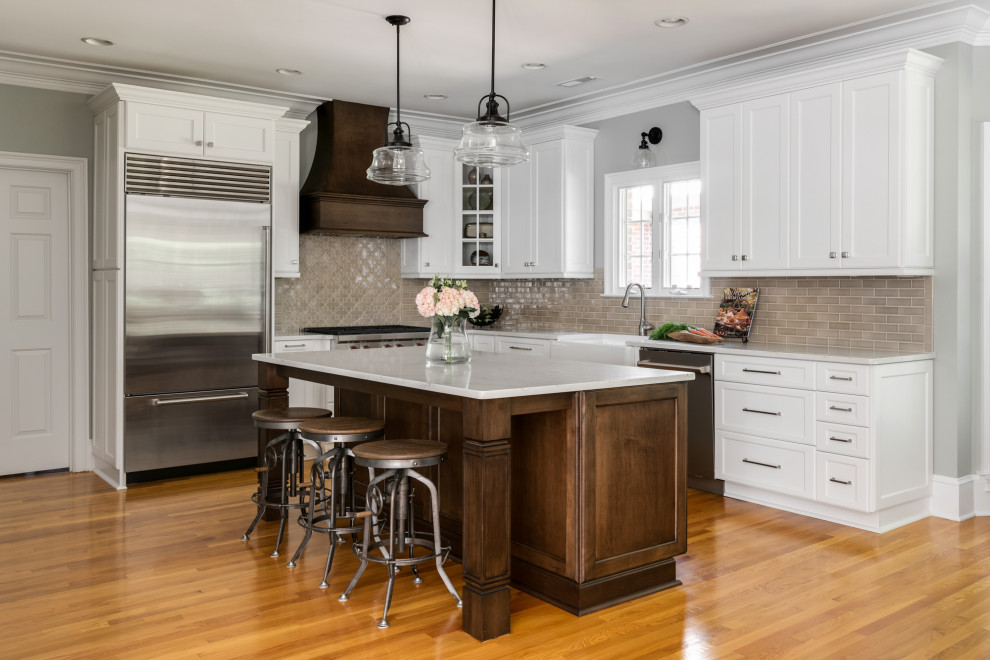 Mid-sized elegant l-shaped light wood floor and brown floor eat-in kitchen photo in Charlotte with a farmhouse sink, shaker cabinets, white cabinets, quartz countertops, brown backsplash, porcelain backsplash, stainless steel appliances, an island and gray countertops