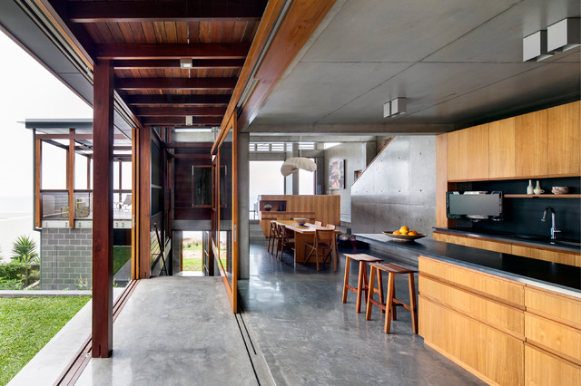 Example of a trendy concrete floor open concept kitchen design in Sydney  with light wood cabinets