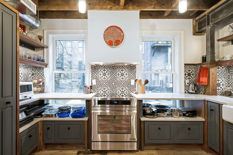 Mid-sized eclectic u-shaped medium tone wood floor and brown floor enclosed kitchen photo in Boston with raised-panel cabinets, gray cabinets, white countertops, multicolored backsplash, a farmhouse sink, solid surface countertops, cement tile backsplash, stainless steel appliances and no island