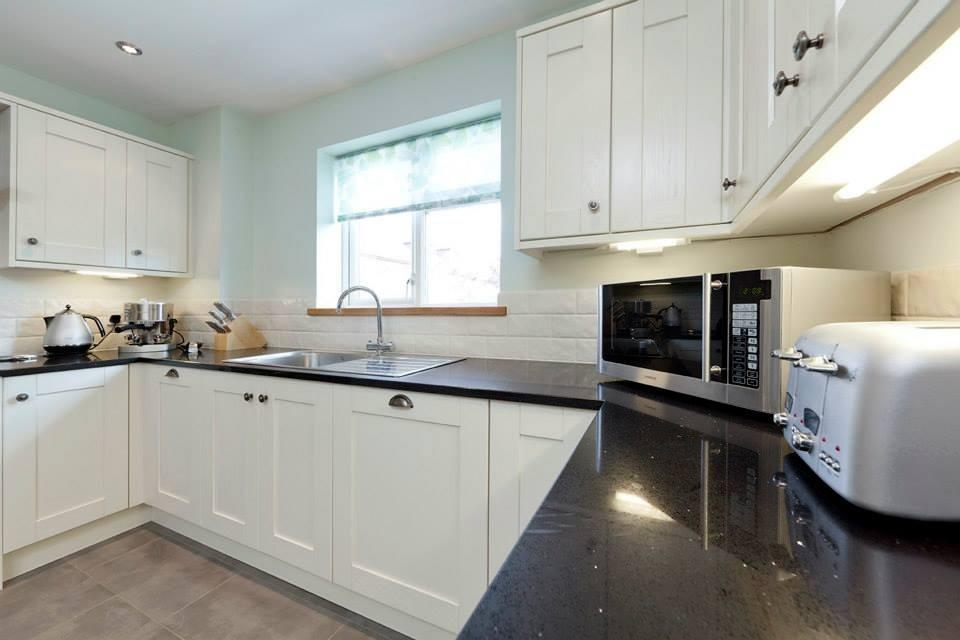 Photo of a large contemporary u-shaped enclosed kitchen in London with a single-bowl sink, shaker cabinets, beige cabinets, quartz worktops, beige splashback, ceramic splashback, black appliances and porcelain flooring.