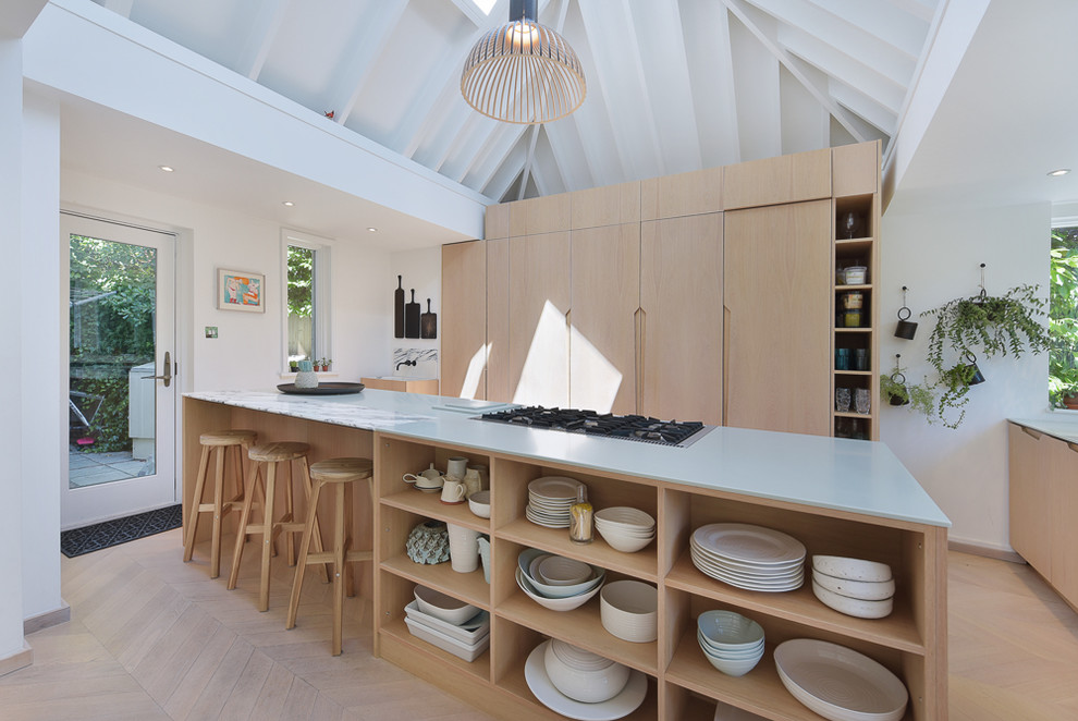 Example of a mid-sized danish light wood floor and beige floor kitchen design in London with flat-panel cabinets, light wood cabinets, marble countertops, an island and gray countertops