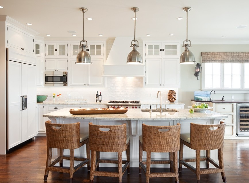 Large coastal l-shaped dark wood floor and brown floor eat-in kitchen photo in New York with an island, beaded inset cabinets, white cabinets, white backsplash, subway tile backsplash, stainless steel appliances, an undermount sink and marble countertops