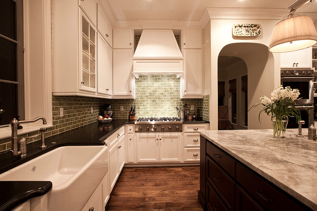 Example of a coastal u-shaped enclosed kitchen design in Tampa with a farmhouse sink, glass-front cabinets, white cabinets, granite countertops, green backsplash, subway tile backsplash and stainless steel appliances