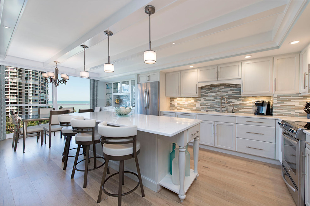 Large beach style l-shaped light wood floor and beige floor open concept kitchen photo in Tampa with an undermount sink, white cabinets, quartz countertops, multicolored backsplash, glass tile backsplash, stainless steel appliances, an island and shaker cabinets