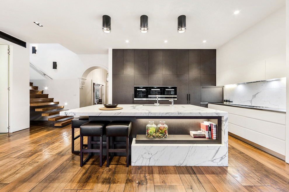 Inspiration for a large contemporary l-shaped eat-in kitchen remodel in Melbourne with an undermount sink, flat-panel cabinets, white cabinets, marble countertops, stone slab backsplash and an island